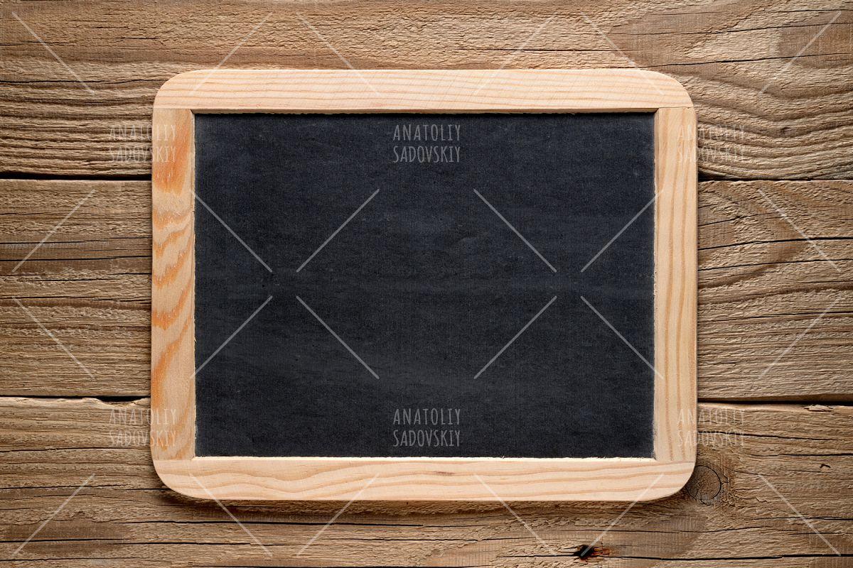 Blackboard in wooden frame on old wood | Design Bundles