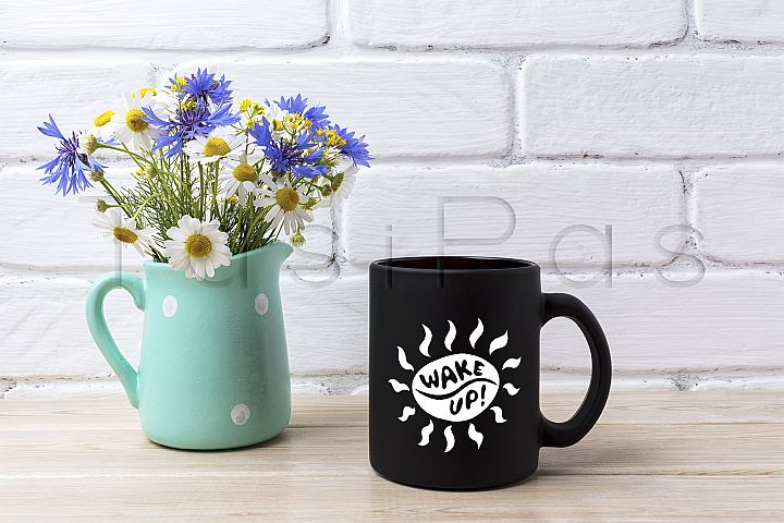Black coffee mug mockup with cornflower and daisy in pitcher