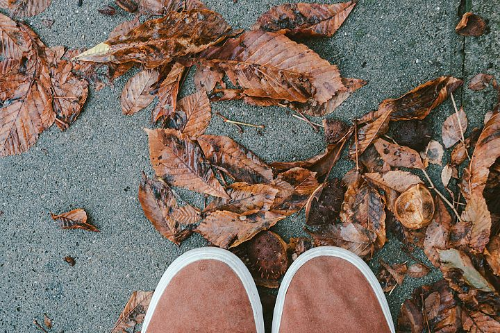 Feet man walking on fall leaves