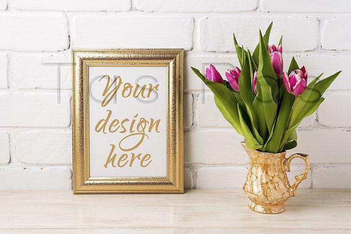 Golden frame mockup with magenta pink tulips in golden vase